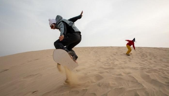 Snowboard Sporcuları Kum Tepelerinde Kum Sörfü Yapmaya Hazırlanıyor